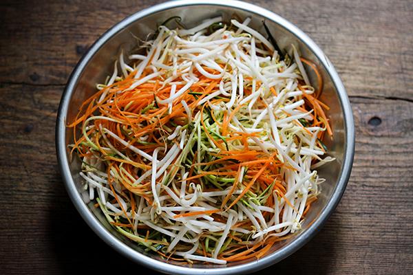Zucchini- und Karottenstreifen mit Mungobohnen-Sprossen mischen