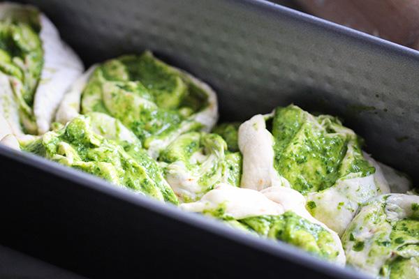 Teig für das Partyzupfbrot gefüllt mit Pesto in die Form schichten.
